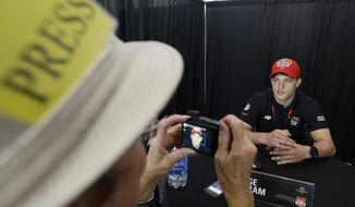 Sage Karam has his photo taken by Lynne Huntting as he responds to a question during a media interview for the Indianapolis 500 IndyCar auto race at the Indianapolis Motor Speedway in Indianapolis, Thursday, May 22, 2014. (AP Photo/Darron Cummings)