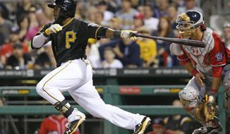 Pittsburgh Pirates' Josh Harrison, left, drives in the go-ahead run with a single off Washington Nationals starting pitcher Stephen Strasburg during the seventh inning of a baseball game in Pittsburgh, Saturday, May 24, 2014. (AP Photo/Gene J. Puskar)