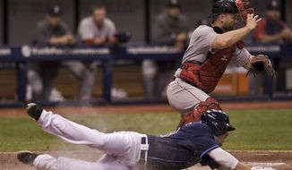 Tampa Bay Rays' Matt Joyce, left, slides past Boston Red Sox catcher David Ross to score on Brandon Guyer's two-run double during the fifth inning of  a baseball game Saturday, May 24, 2014 in St. Petersburg, Fla. (AP Photo/Steve Nesius)