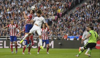 Atletico's Diego Godin, centre left scores the opening goal, during the Champions League final soccer match between Atletico Madrid and Real Madrid, at the Luz stadium, in Lisbon, Portugal, Saturday, May 24, 2014. (AP Photo/Manu Fernandez)