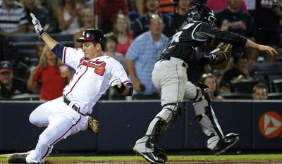Atlanta Braves' Ramiro Pena, left, scores past Colorado Rockies catcher Jordan Pacheco on hit by Gerald Laird to break a 2-2 tie during the eighth inning of a baseball game Friday, May 23, 2014, in Atlanta. (AP Photo/David Tulis)