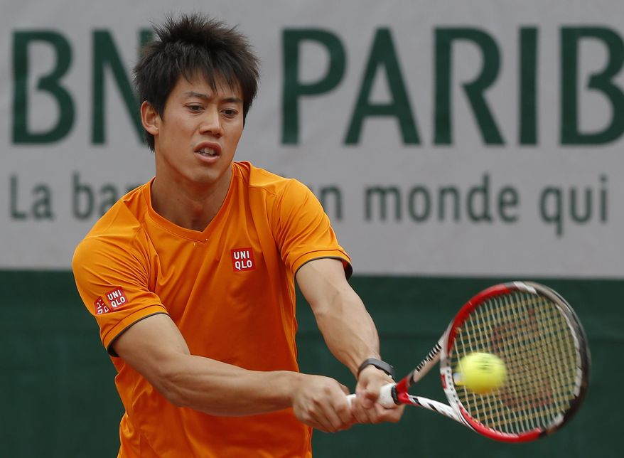 Kei Nishikori, of Japan, returns the ball during a training session for the French Open tennis tournament, at the Roland Garros stadium in Paris, Friday, May 23, 2014. The French Open tennis tournament starts Sunday. (AP Photo/Michel Euler)