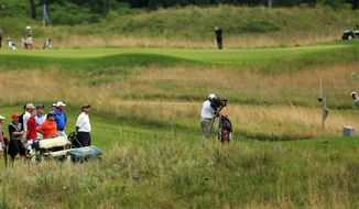 A group of people and a television camera follow Stanford's Patrick Rodgers, right, on the eighth hole during the first round of the NCAA college men's golf championship on Saturday, May 24, 2014, at Prairie Dunes Country Club in Hutchinson, Kan. (AP Photo/The Hutchinson News, Travis Morisse)