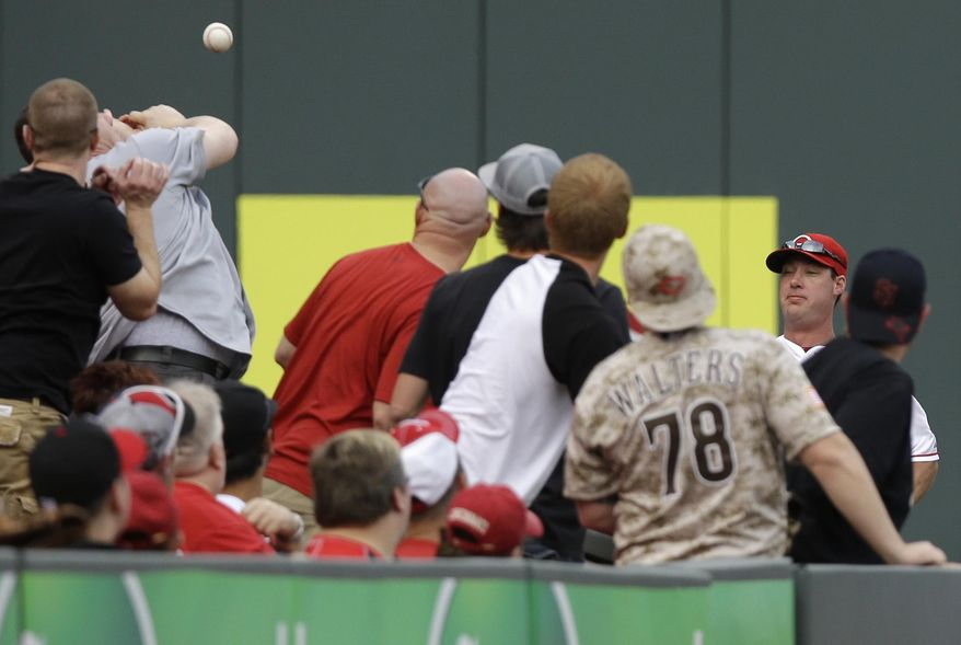 Cincinnati Reds left fielder Ryan Ludwick, right, chases a foul ball hit into the stands in the first inning of a baseball game against the St. Louis Cardinals, Saturday, May 24, 2014, in Cincinnati. (AP Photo/Al Behrman)