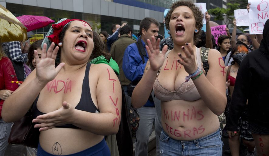 "**FILE** Women chant slogans during the ""SlutWalk,"" an annual protest march against sexual harassment, in Sao Paulo, Brazil, Saturday, May 24, 2014. ""SlutWalk"" protests originated in Toronto, where they were sparked by a police officer's remark that women could avoid being raped by not dressing like ""sluts."" (AP Photo/Andre Penner)"