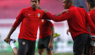 Atletico's Diego Costa, left stretches with teammate Miranda, during a training session ahead of Saturday's Champions League final soccer match between Real Madrid and Atletico Madrid, in Luz stadium in Lisbon, Portugal, Friday, May 23, 2014. (AP Photo/Andres Kudacki)