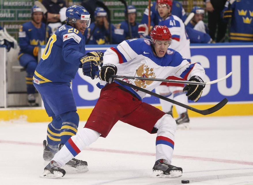 Russia forward Evgeni Malkin, right, battles for the puck with Sweden forward Joel Lundqvist during a semifinal match between Russia and Sweden at the Ice Hockey World Championship in Minsk, Belarus, Saturday, May 24, 2014. (AP Photo/Darko Bandic)