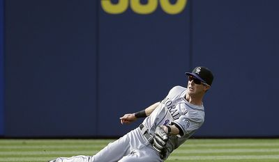 Colorado Rockies' Drew Stubbs makes a sliding catch on a fly out by Atlanta Braves' Ramiro Pena in the fourth inning of a baseball game, Saturday, May 24, 2014, in Atlanta. (AP Photo/David Goldman)