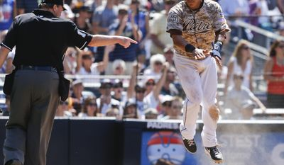 San Diego Padres' Everth Cabrera pops up from his slide at home plate umpire Gerry Davis points to the plate during a four-run rally against the Chicago Cubs in the sixth inning of a baseball game, Sunday, May 25, 2014, in San Diego. (AP Photo/Lenny Ignelzi)