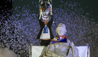 Real Madrid's Sergio Ramos lifts the trophy next to the Cibeles statue in Madrid, Spain, Sunday, May 25, 2014, after the team won the Champions League final soccer match in Lisbon by beating Atletico Madrid. (AP Photo/Paul White)