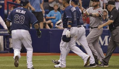 Boston Red Sox left fielder Jonny Gomes, second right, rushes past umpire Larry Vanover, right, toward Tampa Bay Rays' Jose Molina (28) Yunel Escobar (11) and third base coach Tom Foley (66) at the start of a benches-clearing brawl during the seventh inning of a baseball game Sunday, May 25, 2014 in St. Petersburg, Fla. (AP Photo/Steve Nesius)