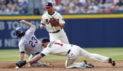 Colorado Rockies shortstop Charlie Culberson (23) is safe at second base on a D.J. LeMahieu ground ball as Atlanta Braves second baseman Tyler Pastornicky (1) mishandles the ball inning of a baseball game Sunday, May 25, 2014 in Atlanta. Pastronicky was chargesd with an error on the play. Atlanta Braves second baseman Tyler Pastornicky (1) looks on in the background. (AP Photo/John Bazemore)