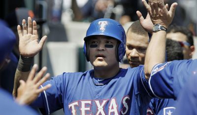 Texas Rangers' Shin Soo-Choo, of South Korea, is congratulated in the dugout after scoring against the Detroit Tigers on a single by Mitch Moreland during the fifth inning of a baseball game Sunday, May 25, 2014, in Detroit. (AP Photo/Duane Burleson)