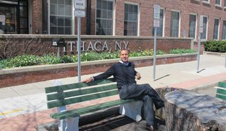 This April 24, 2014, shows Ithaca, N.Y. Mayor Svante Myrick sitting on a bench in his parking spot, which he transformed into a public park in Ithaca, N.Y.  Myrick says he draws heavily on life experience as he shapes public policy, which may seem odd for someone still only in his 20s.  The city's youngest-ever mayor says his approach to Ithaca's budget gap and even homeless population can be traced to a childhood that took him from a homeless shelter to the Ivy League.  (AP Photo/Carolyn Thompson)