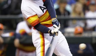 Houston Astros' George Springer hits a two-run home run against the Seattle Mariners in the fifth inning of a baseball game Saturday, May 24, 2014, in Seattle. (AP Photo/Elaine Thompson)