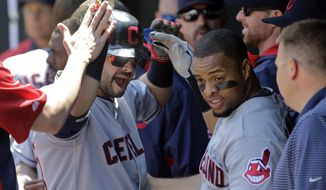 Cleveland Indians' Nick Swisher, left, and Carlos Santana high-five teammates in the dugout after Santana scored on Swisher's sacrifice fly ball in the first inning of a baseball game against the Baltimore Orioles, Sunday, May 25, 2014, in Baltimore. (AP Photo/Patrick Semansky)