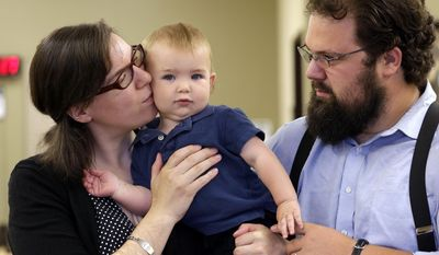 In this May 21, 2014 photo, Amanda Lewis, left, gives her son Fletcher, 1, a kiss as her husband Ivan looks on while being photographed in Mukilteo, Wash. The family has long used a naturopathic doctor, covered by their private insurance plan, as their primary care provider. But up until this year, Lewis had to pay $95 a visit for her young son because naturopaths in Washington state weren't authorized to be part of the Medicaid plan that he was covered under. (AP Photo/Elaine Thompson)