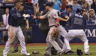 Boston Red Sox first baseman Mike Carp, center, confronts Tampa Bay Rays' Yunel Escobar, left, during a seventh- inning brawl of a baseball game against the Tampa Bay Rays Sunday, May 25, 2014 in St. Petersburg, Fla. Boston's Jonny Gomes was ejected along with Carp and Escobar. (AP Photo/Steve Nesius)