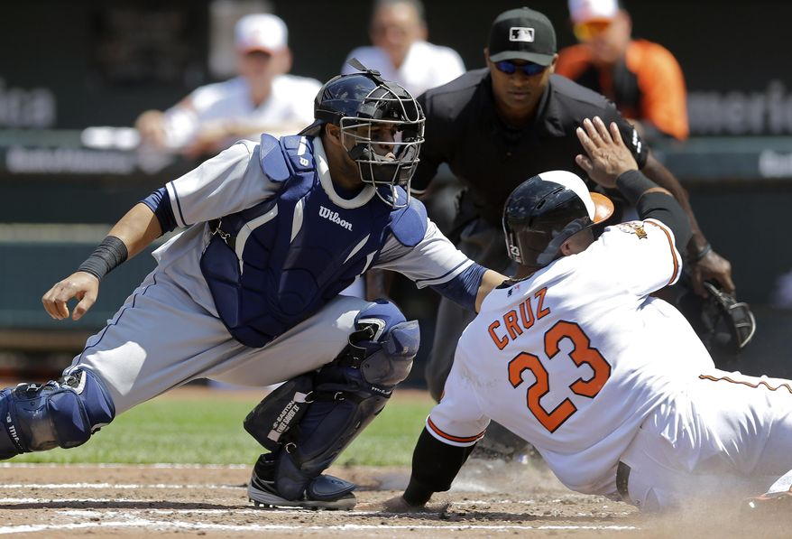 Cleveland Indians catcher Carlos Santana, left, tries to tag Baltimore Orioles' Nelson Cruz (23) at home plate on a single hit by Steve Pearce in the third inning of a baseball game on Sunday, May 25, 2014, in Baltimore. Cruz was safe after Santana lost control of the ball. (AP Photo/Patrick Semansky)