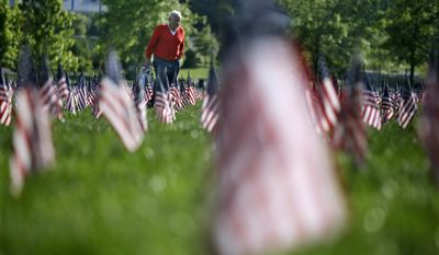John Walaszek, of Old Bridge, N.J., is surrounded by flags for Memorial Day, as he visits his wife's grave at Brig. Gen. William C. Doyle Veterans Memorial Cemetery in Wrightstown, N.J., Sunday, May 25, 2014. (Mel Evans)