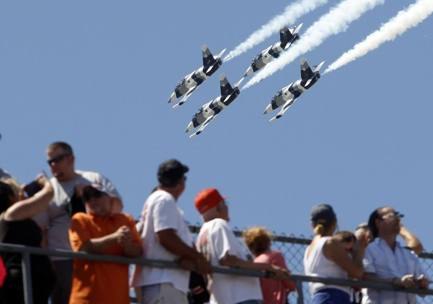Fans watch as four L-39 Albatros high-performance jet trainer aircraft  flown by the Black Diamond Jet Team, a civilian-owned aerobatic jet team perform a fly-over during the National Anthem before the start of the 98th running of the Indianapolis 500 IndyCar auto race at the Indianapolis Motor Speedway in Indianapolis, Sunday, May 25, 2014. (AP Photo/Tom Strattman)