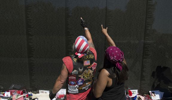 Dave Wehner, left, of Pittsburgh and Veronica Allen look for names on the Vietnam Veterans Memorial in Washington, Sunday, May 25, 2014. (AP Photo/Molly Riley)