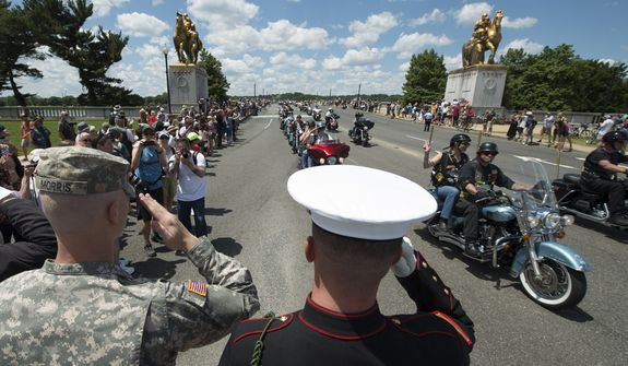 Army Pfc. Colin Morris, left, and Marine Cpl. Zach Powers, center, salute participates of Rolling Thunder 'Ride for Freedom' event in Washington, Sunday, May 25, 2014. (AP Photo/Molly Riley)