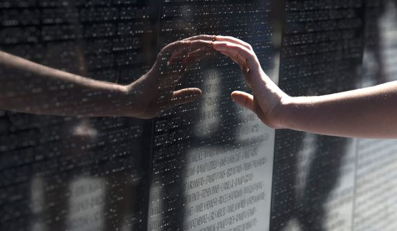 A visitor touches a name on the Vietnam Veterans Memorial in Washington, Sunday, May 25, 2014. (AP Photo/Molly Riley)