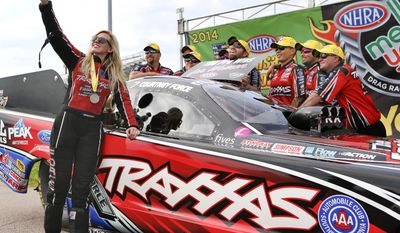 Funny Car driver Courtney Force takes a photo with her team after her championship run that gave her the 100th victory by a female driver in NHRA history at the NHRA Kansas Nationals drag races on Sunday, May 25, 2014, at Heartland Park in Topeka, Kan. (AP Photo/Topeka Capital-Journal, Chris Neal)