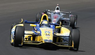 Marco Andretti leads Scott Dixon, of New Zealand, through the first turn during the 98th running of the Indianapolis 500 IndyCar auto race at the Indianapolis Motor Speedway in Indianapolis, Sunday, May 25, 2014. (AP Photo/Tom Strattman)