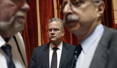 In this April 30, 2014 photo, Rhode Island House Speaker Nicholas Mattiello, center, stands near reporter Jim Baron, left, and House spokesman Larry Berman, right, on the floor of the House Chamber before going into session at the Statehouse, in Providence, R.I. Mattiello is a centrist Democrat and former majority leader whose meteoric rise to the position followed the downfall of Gordon Fox. (AP Photo/Steven Senne)