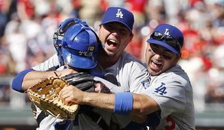 Los Angeles Dodgers starting pitcher Josh Beckett, center, celebrates with catcher Drew Butera, left, and first baseman Adrian Gonzalez after pitching a no-hitter baseball game against the Philadelphia Phillies, Sunday, May 25, 2014, in Philadelphia. Los Angeles won 6-0. Beckett pitched the first no-hitter of his career and the first in the majors this season. (AP Photo/Matt Slocum)