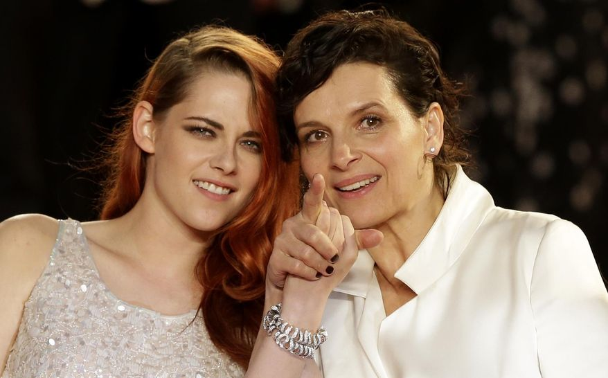 Actress Kristen Stewart, left, and actress Juliette Binoche pose for photographers following the screening of Sils Maria at the 67th international film festival, Cannes, southern France, Friday, May 23, 2014. (AP Photo/Thibault Camus)