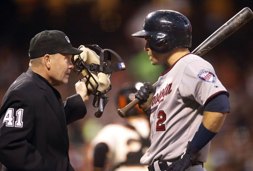 Minnesota Twins' Brian Dozier (2) argues with home plate umpire Jerry Meals after striking out against the San Francisco Giants in the fifth inning of a baseball game Saturday, May 24, 2014, in San Francisco. (AP Photo/Tony Avelar)