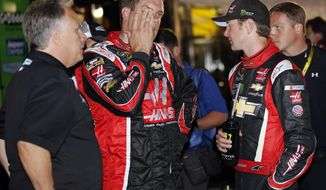 Driver Kurt Busch, right, talks to a crew member, center, and team owner Carl Haas, left, after dropping out of the NASCAR Sprint Cup series Coca-Cola 600 auto race at Charlotte Motor Speedway in Concord, N.C., Sunday, May 25, 2014. (AP Photo/Terry Renna)