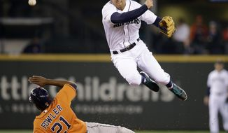 Seattle Mariners shortstop Brad Miller, right, leaps out of the way after forcing out Houston Astros' Dexter Fowler at second base in the fourth inning of a baseball game Sunday, May 25, 2014, in Seattle. Miller completed the play to first for the double play. (AP Photo/Elaine Thompson)
