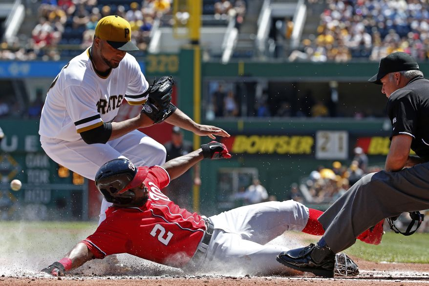Washington Nationals' Denard Span (2) scores from third on a wild pitch by Pittsburgh Pirates starting pitcher Francisco Liriano, left, as umpire Tim Timmons watches the play during the first inning of a baseball game in Pittsburgh Sunday, May 25, 2014. (AP Photo/Gene J. Puskar)