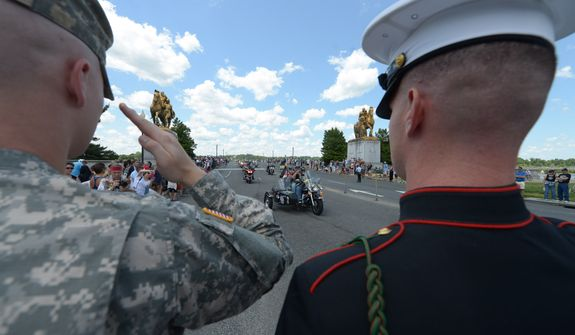 Soldiers salute motorcycle riders participating in the 25th anniversary of the Rolling Thunder Ride for Freedom at the base of the Memorial Bridge on Sunday, May 25. Khalid Naji-Allah/ Special for the Washington Times