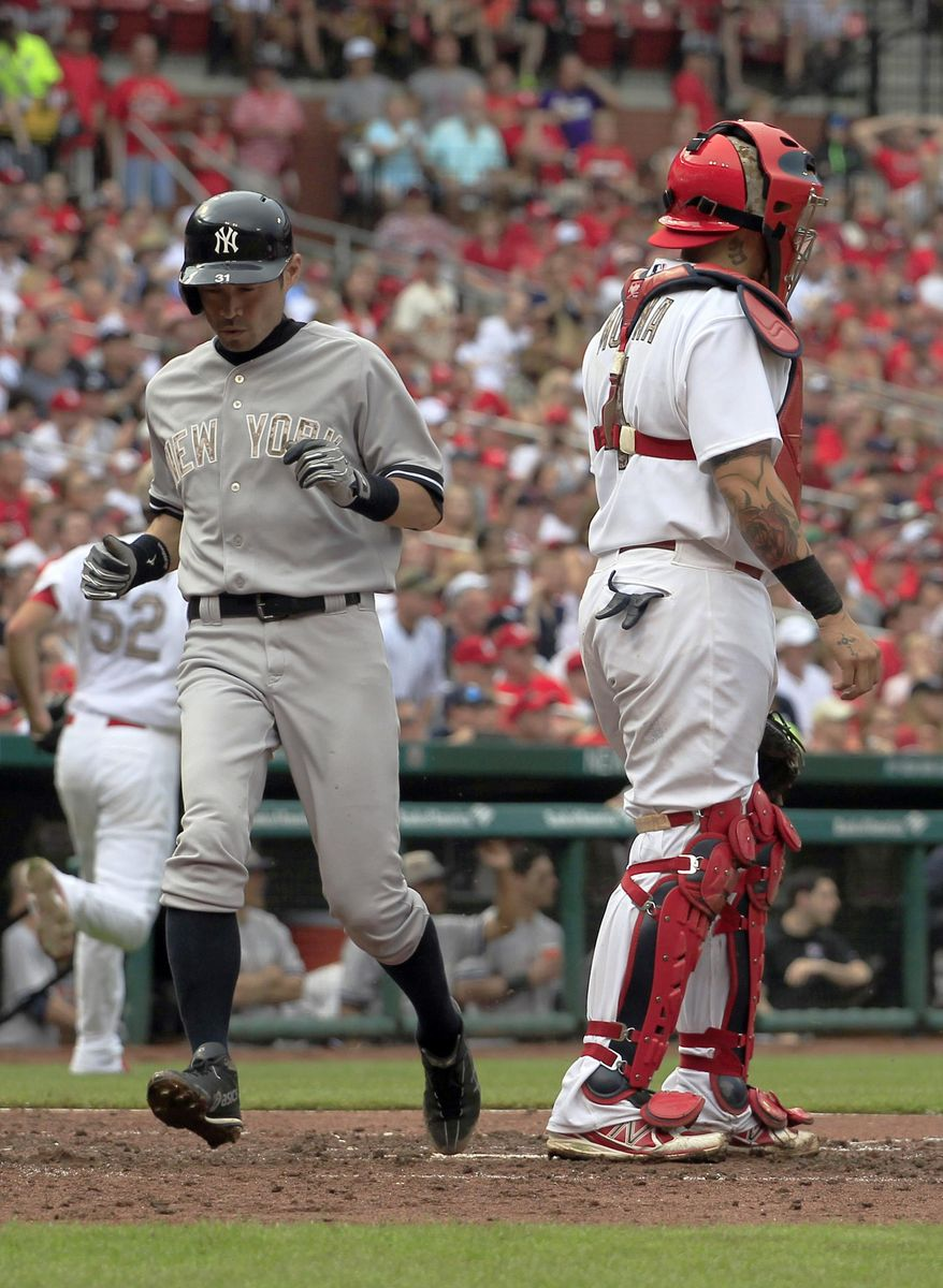 New York Yankees' Ichiro Suzuki, left, scores on a single by Kelly Johnson as St. Louis Cardinals catcher Yadier Molina stands by during the fifth inning of a baseball game Monday, May 26, 2014, in St. Louis. (AP Photo/Jeff Roberson)