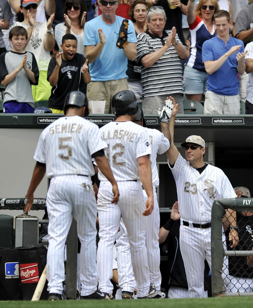 Chicago White Sox manager Robin Ventura, (23), celebrates with Dayan Viciedo in the dugout after Viciedo hit a three run home run during the third inning of a baseball game against the Cleveland Indians in Chicago, Monday, May 26, 2014. (AP Photo/Paul Beaty)