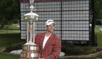 Adam Scott posses with the champion's trophy after winning the PGA Colonial golf tournament in Fort Worth, Texas, Sunday, May 25, 2014. (AP Photo/LM Otero)