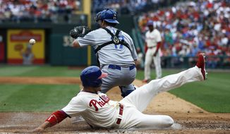 Philadelphia Phillies' Cesar Hernandez, bottom, scores past Los Angeles Dodgers catcher A.J. Ellis on a single by Ben Revere during the second inning of a baseball game, Saturday, May 24, 2014, in Philadelphia. (AP Photo/Matt Slocum)