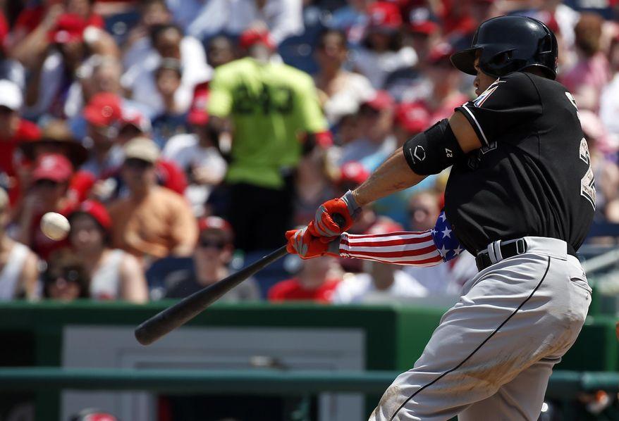 Miami Marlins' Giancarlo Stanton hits a two-run homer during the third inning of a baseball game against the Washington Nationals at Nationals Park Monday, May 26, 2014, in Washington. (AP Photo/Alex Brandon)