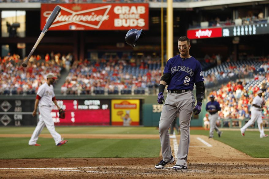 Colorado Rockies' Troy Tulowitzki, right, tosses his bat and helmet after striking out against Philadelphia Phillies relief pitcher Mike Adams to end the seventh inning of a baseball game, Monday, May 26, 2014, in Philadelphia. Philadelphia won 9-0. (AP Photo/Matt Slocum)