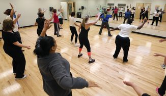 In this April 18, 2014 photo, people take part in a Bokwa fitness class at the Healthy Living Center located in a Hannaford supermarket in Albany, N.Y. The idea for the in-store gym grew out of a meeting last summer between Hannaford, the local YMCA and the health care provider Capital District Physicians' Health Plan. All said their goal was to come up with something to improve the area's health while also being convenient, accessible and free.  (AP Photo/Mike Groll)