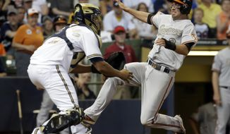 Baltimore Orioles' J.J. Hardy scores past Milwaukee Brewers catcher Martin Maldonado during the 10th inning of a baseball game Monday, May 26, 2014, in Milwaukee. Hardy scored from second on a hit by Nick Hundley. (AP Photo/Morry Gash)
