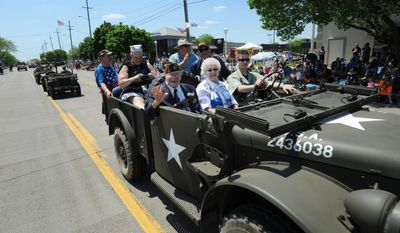 A contingent of army vehicles carrying veterans makes its way north on Harper Ave. during the 62nd annual Memorial Day parade in St. Clair Shores, Mich., on Sunday, May 25, 2014.(AP Photo/Detroit News, Brandy Bakerr)  DETROIT FREE PRESS OUT; HUFFINGTON POST OUT   MBO  (REV-SHARE)