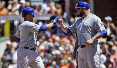 Chicago Cubs' Welington Castillo, left, is high fived by first base coach Eric Hinske after Castillo's RBI single against the San Francisco Giants during the sixth inning of a baseball game on Monday, May 26, 2014, in San Francisco. (AP Photo/Marcio Jose Sanchez)