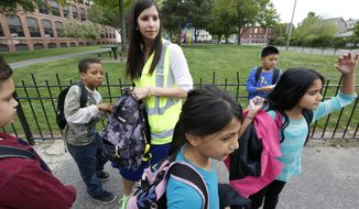 In May 20, 2014 photo, eight-year-old Divya Dahal, center front, takes a break with other school children while walking home from school with a group of kids escorted by Allyson Trenteseaux, a Walking School Bus program manager, top, in Providence, R.I. Program is seen as a way to get kids active, fight childhood obesity and improve absenteeism, which can be higher among students who live too close to school to qualify for a bus ride. (AP Photo/Steven Senne)