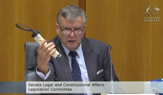 In this image made from ABC video, Sen. Bill Heffernan shows a fake pipe bomb during a committee hearing in Canberra, Australia, Sunday, May 25, 2014. Heffernan, who represents the ruling Liberal Party, was making a point about a relaxation of security at Parliament House. (AP Photo/ABC via AP Video) AUSTRALIA OUT
